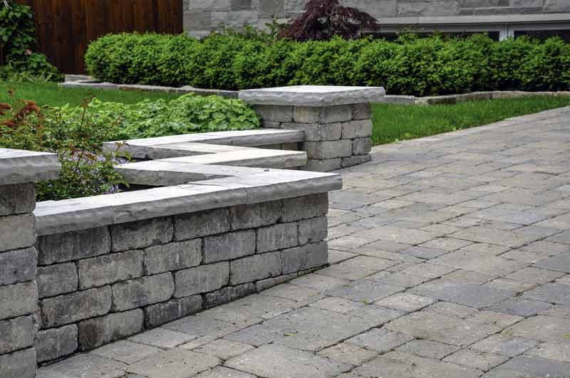 a huge patio and retaining wall made out of paver blocks surrounded by beautifully green shrubs and grass